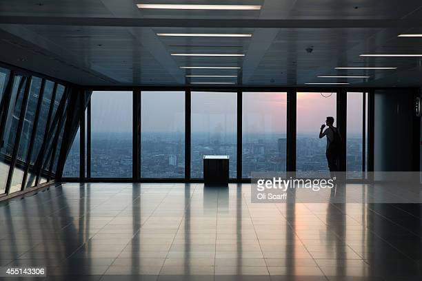 A man looks out at the London skyline from an upper floor of a newly constructed skyscraper The Leadenhall Building as the sun sets on September 9...