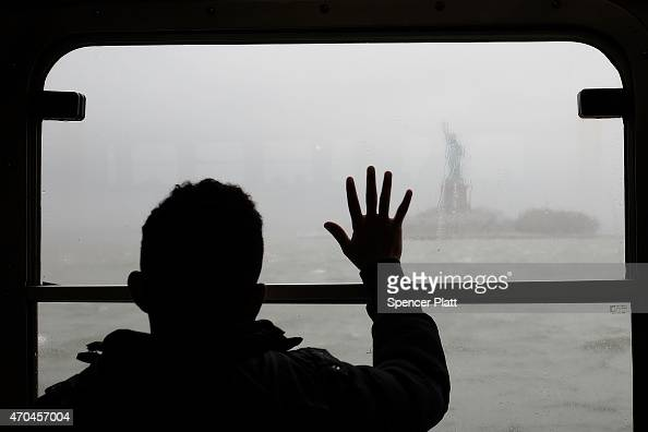 A man looks out at the Statue of Liberty in the rain and fog from the Staten Island Ferry on April 20 2015 in New York City Much of the East Coast...