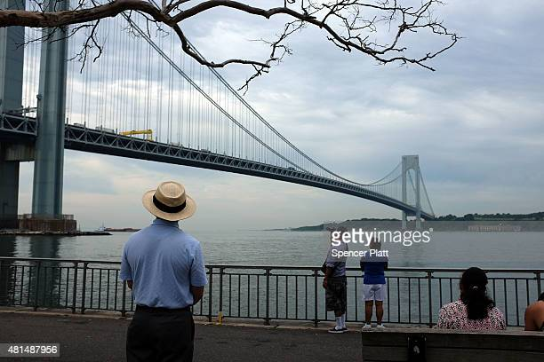 A man looks out at the Verrazano Bridge from a pedestrian promanade on a sultry morning in Brooklyn on July 21 2015 in New York City Despite an...