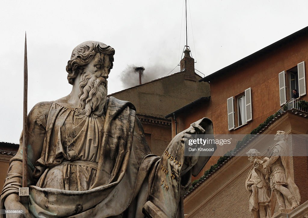 A man looks out from a window near to the statue of St Paul as black smoke billows from the chimney on the roof of the Sistine Chapel indicating that the College of Cardinals have failed to elect a new Pope on March 13, 2013 in Vatican City, Vatican. Pope Benedict XVI's successor is being chosen by the College of Cardinals in Conclave in the Sistine Chapel. The 115 cardinal-electors, meeting in strict secrecy, will need to reach a two-thirds-plus-one vote majority to elect the 266th Pontiff.