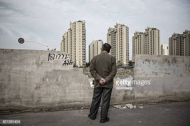 A man looks out from an opening in a wall as residential buildings stand in the distance in the Jiading district of Shanghai China on Monday April 11...