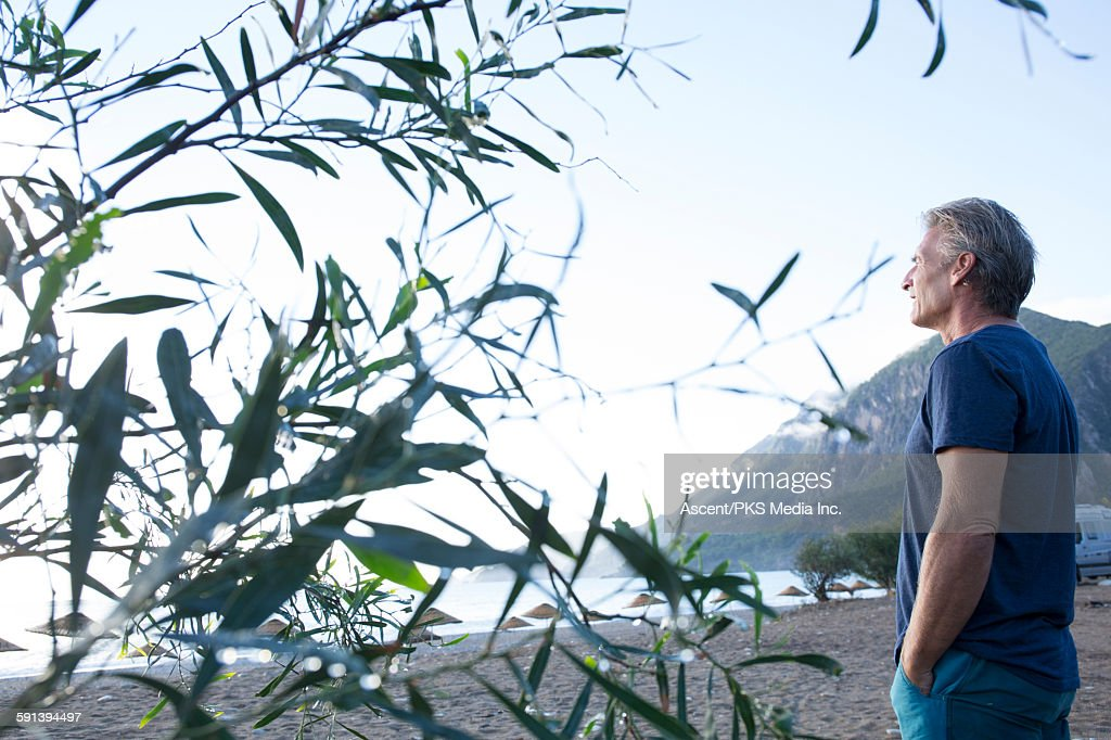 Man looks out from beach to sea, vehicle behind