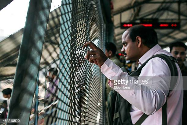 A man looks out from behind a fence on a footbridge at Kurla railway station in Mumbai India on Saturday Feb 21 2015 Indian Railways is scheduled to...