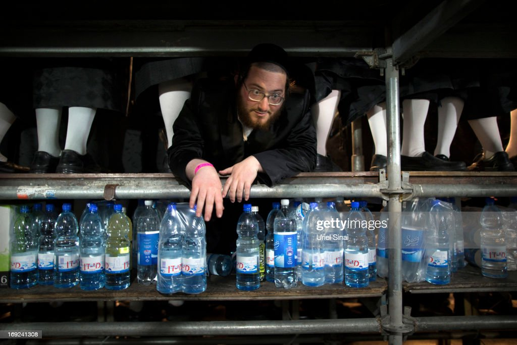 A man looks out from between feet of his freinds as tens of thousands of Ultra-Orthodox Jews of the Belz Hasidic Dynasty take part in the wedding ceremony of Rabbi Shalom Rokach, the Grandson of the Belz Rabbi to Hana Batya Pener, early morrning of May 22, 2013. in Jerusalem, Israel. Some 25,000 Ultra-Orthodox Jews participated in one of the biggest weddings of the of Ultra-Orthodox Jewish community in the past few years.