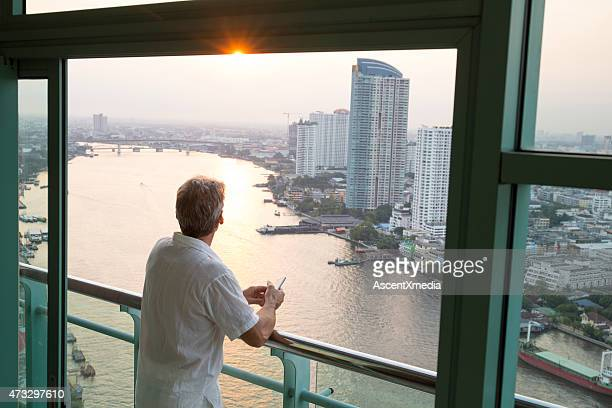 Man looks out from hotel railing, above city, river