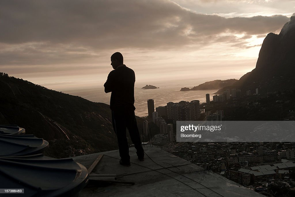 A man looks out from the rooftop of a neighbor's house in the Rocinha slum of Rio de Janeiro, Brazil, on Wednesday, Nov. 28, 2012. About 56 percent of the 12 million people who live in slums like Rocinha were considered middle class in 2011, up from 29 percent in 2001, according to a study this year by Instituto Data Popular, a Sao Paulo-based research group. Photographer: Dado Galdieri/Bloomberg via Getty Images