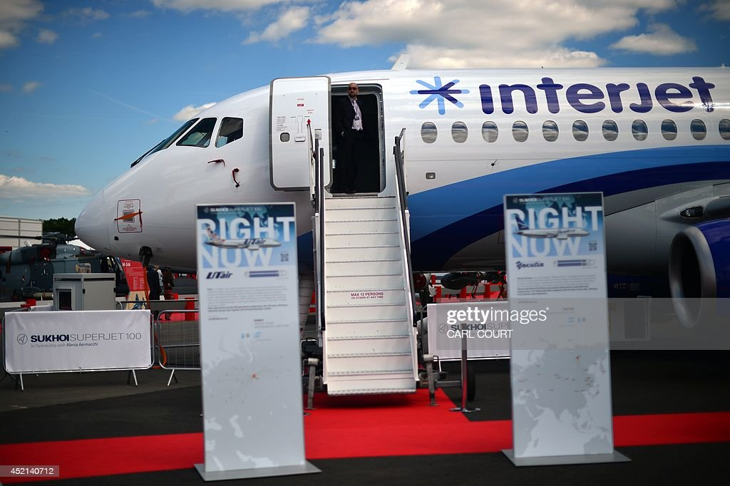 A man looks out from the steps leading to a Sukhoi Superjet 100 at the Farnborough air show in Hampshire England on July 14 2014 The biennial event...