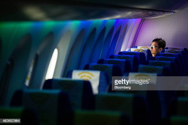 A man looks out of the window of a Boeing Co 787 Dreamliner aircraft operated by Scoot Pte a unit of Singapore Airlines Ltd during a media tour at...