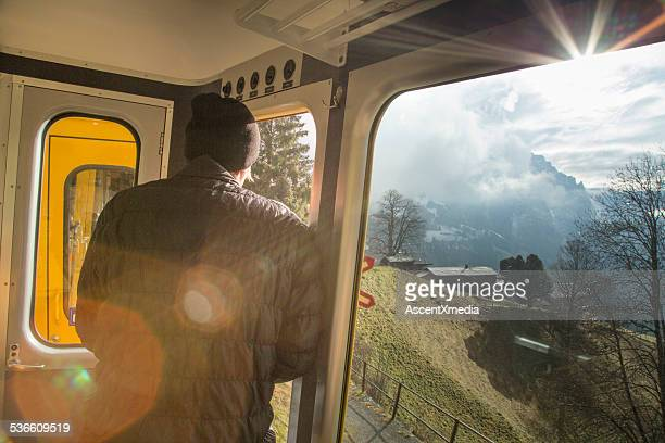 Man looks out of train car to mountains and sunrise