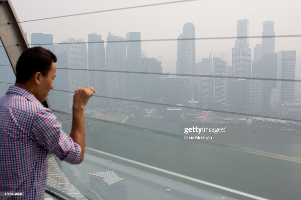 A man looks out over the smoke filled Singapore skyline on June 20, 2013 in Singapore. The Pollutant Standards Index (PSI) rose to the highest level on record reaching 371 at 1pm. The haze is created by deliberate slash-and-burn forest fires started by companies in neighbouring Sumatra.