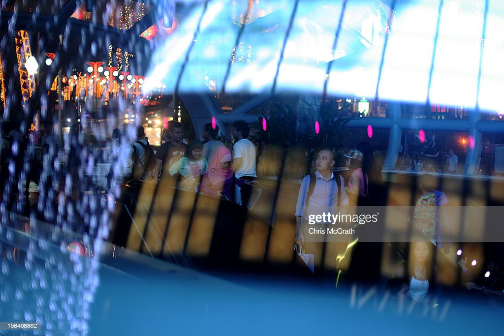 A man looks out to a Christmas lights show as he rides the escalator to the subway at Orchard road on December 17, 2012 in Singapore.