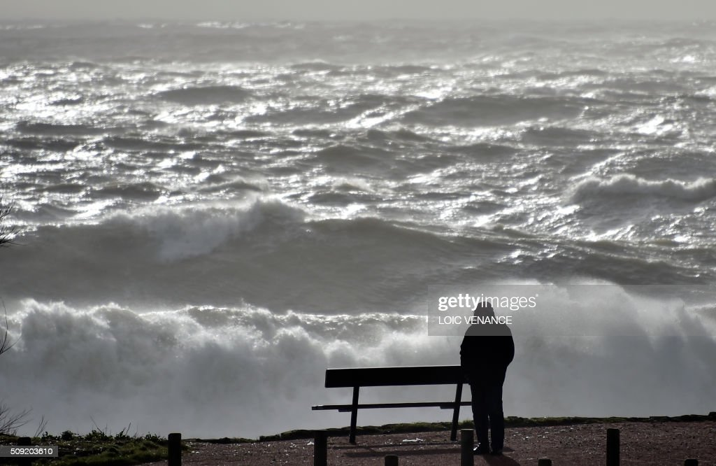 A man looks out to the sea in Les Sables-d'Olonne, western France, on February 9, 2016. High winds buffeted northwestern Europe on February 8, leaving one woman in France in a coma after she was hit by an advertising hoarding. Electricity was cut to 5,000 homes in northern France. / AFP / LOIC VENANCE