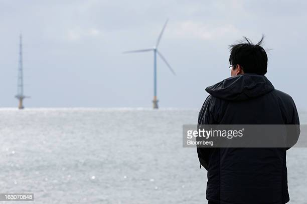 A man looks out towards a 24megawatt wind turbine developed by New Energy and Industrial Technology Development Organization in a joint research...