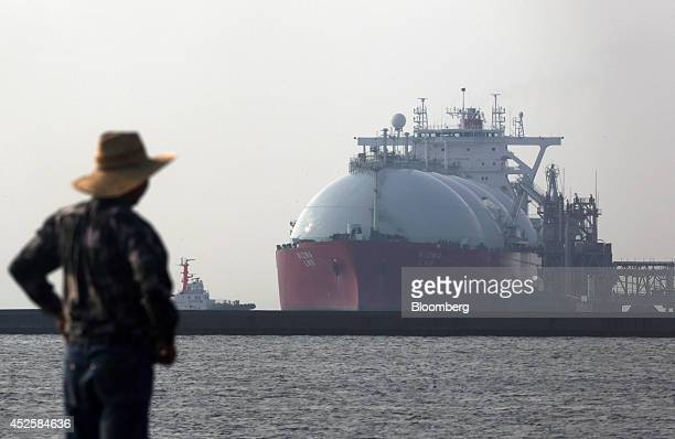 A man looks out towards a liquefied natural gas tanker berthed at Tokyo Electric Power Co's Futtsu gasfired thermal power plant in Futtsu Chiba...