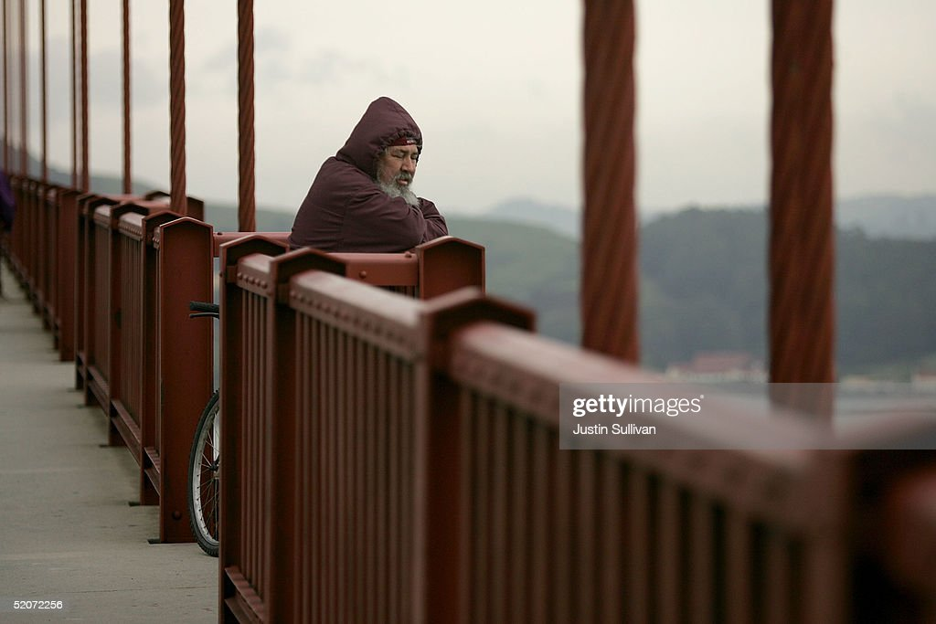 A man looks over the railing of the Golden Gate Bridge January 27, 2005 in San Francisco. A controversial film made by moviemaker Eric Steel documenting people committing suicide off of the Golden Gate Bridge has opened a debate about why there isn't a suicide barrier on the famous landmark. Over 1,300 people have jumped to their death from the span since the bridge opened in 1937.