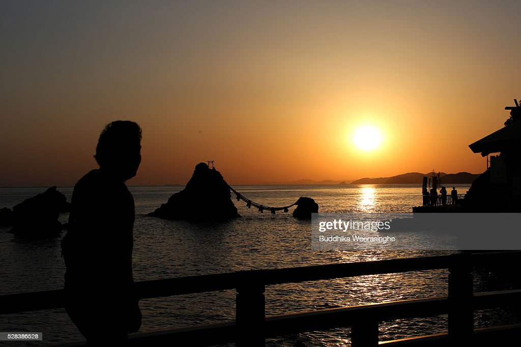 A man looks sun rise over the 'Meoto-Iwa' or couple rocks and over the sea ahead of the Oshimenawahari ceremony at Futami Okitama Shrine on May 5, 2016 in Ise, Japan. The Oshimenawahari ceremony is held three times a year to exchange the 35 meters long heavy rope made of rice straw that connects the sacred Couple Rock - one small, one big. The Couple Rock serves as a gate to the Okitama Shrine, dedicated to the god Sarutahiko and goddess Ukanomitama from Japanese myth.