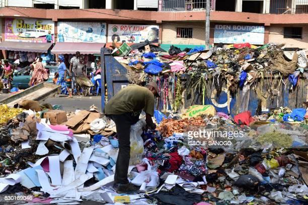 A man looks through a trash heap at the market of Adjame a working class neighbourhood of Abidjan on August 10 2017 / AFP PHOTO / ISSOUF SANOGO