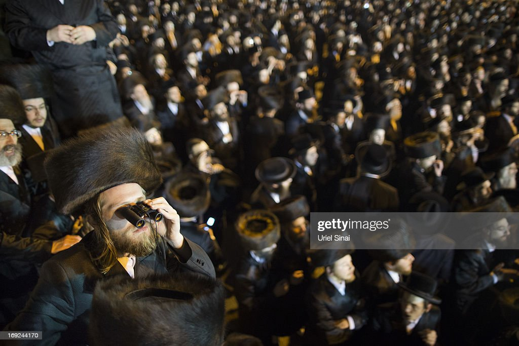 A man looks through binoculars as tens of thousands of Ultra-Orthodox Jews attend the wedding of Rabbi Shalom Rokeach, the grandson of the leader of the Belz Rebbe Hasidic dynasty to Hana Batya Pener on May 21, 2013 in Jerusalem, Israel. Some 25,000 Ultra-Orthodox Jews attended one of the biggest weddings in the Ultra-Orthodox Jewish community in the past few years.
