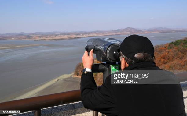 A man looks through binoculars towards North Korea from a South Korean observation post in Paju near the Demilitarized Zone dividing the two Koreas...