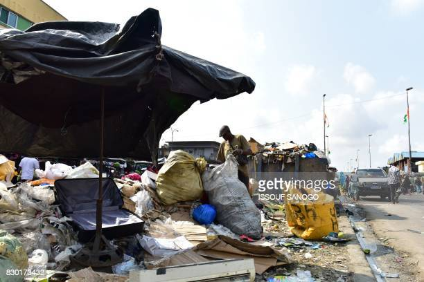 A man looks through rubbish in a trash heap at the market of Adjame a working class neighbourhood of Abidjan on August 10 2017 / AFP PHOTO / ISSOUF...