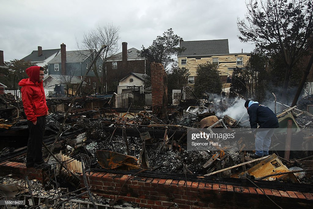 A man looks through the debris of his destroyed home after Hurricane Sandy on October 30, 2012 in the Rockaway section of the Queens borough of New York City. At least 40 people were reportedly killed in the U.S. by Sandy as millions of people in the eastern United States have awoken to widespread power outages, flooded homes and downed trees. New York City was hit especially hard with wide spread power outages and significant flooding in parts of the city.