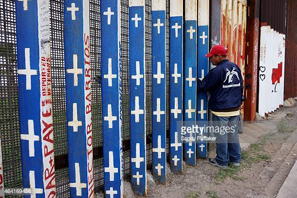 A man looks through the fence along the USMexico border wall on February 22 2015 in Tijuana Mexico Senior Republican senators said they expected...