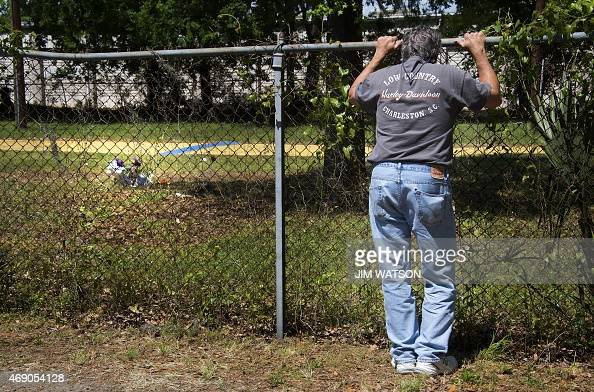 A man looks through the fence at a vacant lot near the area where Walter Scott was killed in North Charleston South Carolina April 9 2015 There were...