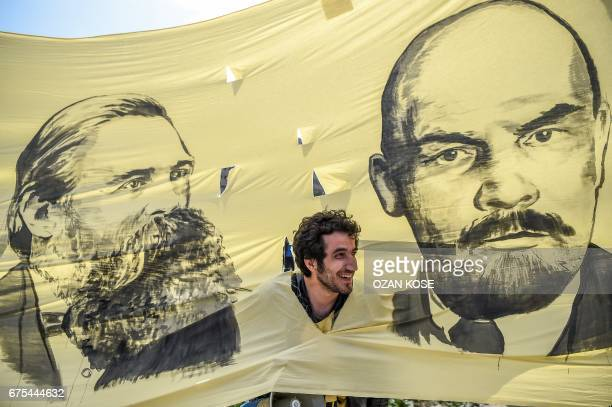 TOPSHOT A man looks through the hole of a banner picturing German philosopher and communist thinker Friedrich Engels and Soviet leader Vladimir...