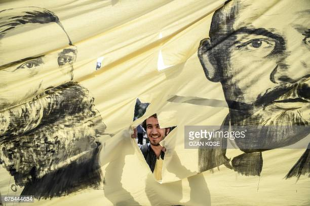 A man looks through the hole picturing German philosopher and communist thinker Friedrich Engels and Soviet leader Vladimir Ilitch Lenin while he...