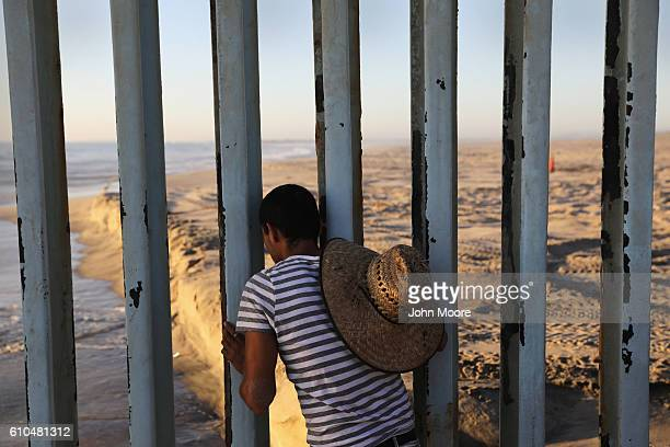 A man looks through the USMexico border fence into the United States on September 25 2016 in Tijuana Mexico Friendship Park on the border is one of...