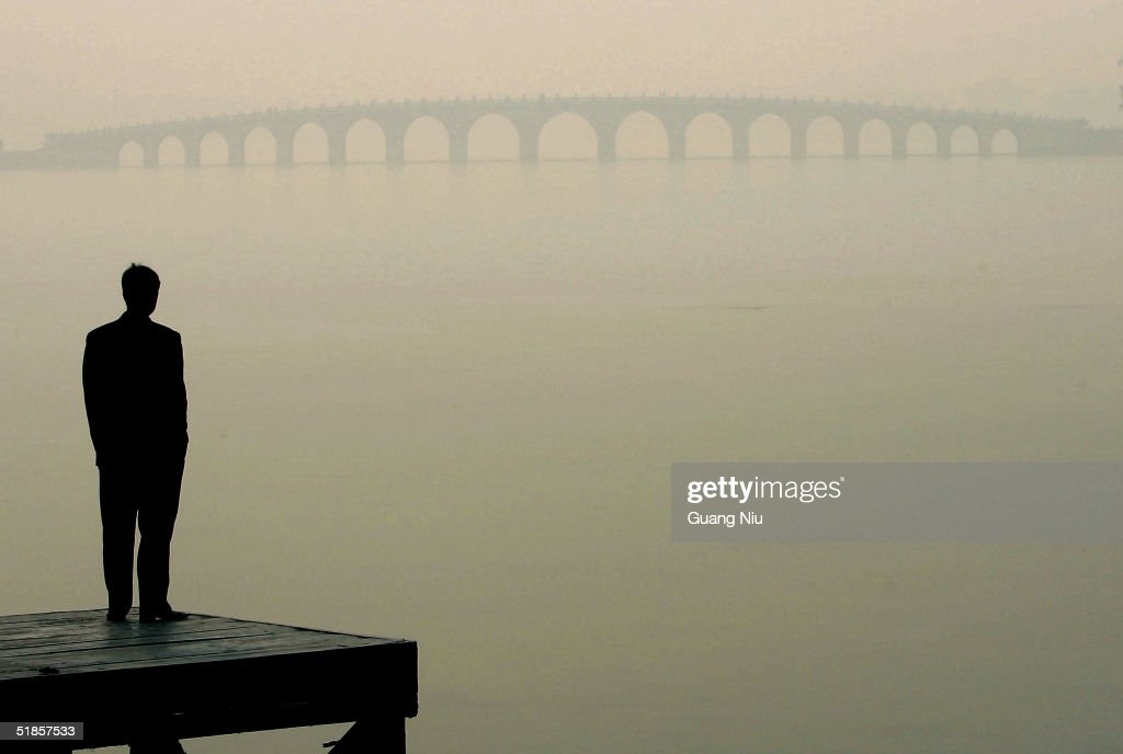 A man looks towards a bridge in heavy fog on December 14, 2004 in Beijing, China. The bad weather has made it harder for Beijing to achieve the target of 18 clear-sky days in December, laid out by the environmental protection campaign, which requires the capital to have clear sky for 62 percent of the year, equivalent to 227 days. Beijing has pledged to cleanse the skies before the 2008 Olympic Games.