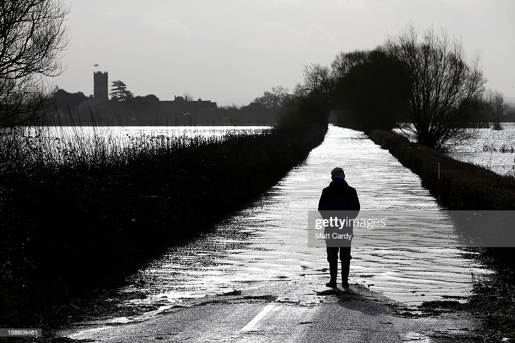A man looks towards the village of Muchelney which has been cut off by flooding on the Somerset Levels on December 30, 2012 near Langport, England. The Met Office is warning of the risk of further flooding towards the end of the year, meaning 2012 is set to be the wettest on record.