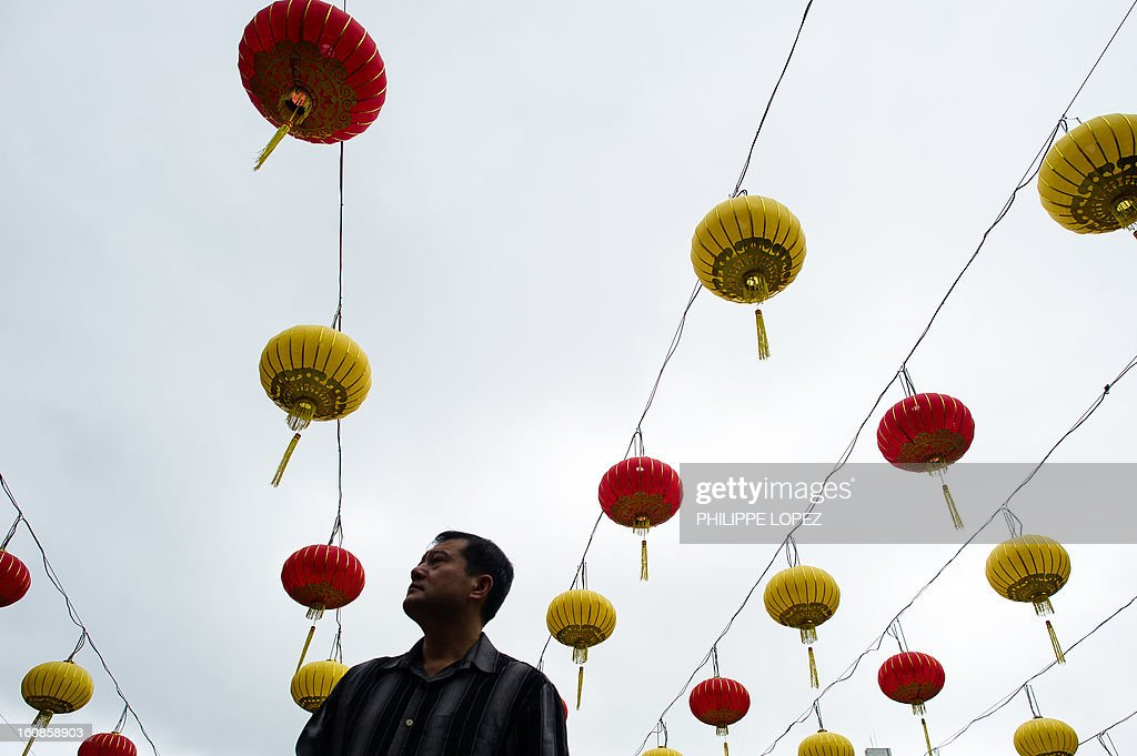 A man looks up at a display of lanterns at a Taoist temple in Hong Kong in Hong Kong on February 7, 2013. A stock market slide, escalated conflict between Japan and China and more Gangnam-styled success for South Korean singer Psy will shape the incoming Year of the Snake, say Asian soothsayers. February 10 marks the first day of the Lunar New Year across the region. AFP PHOTO / Philippe Lopez