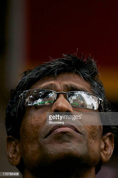 A man looks up at an electronic ticker board displaying the latest stock prices at the Bombay Stock Exchange in Mumbai India on Tuesday June 18 2013...