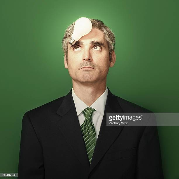 Man looks upward at a lightbulb on his forehead