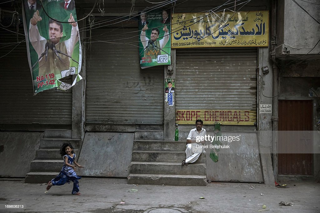 A man loos on as a girl runs down an alleyway hung with election campaign posters from the PML-N party, the day after election day on May 12, 2013 in the Old City of Lahore, Pakistan. The electoral committee recorded a high voter turn out as millions of Pakistanis cast their votes in yesterdays parliamentary elections. It is the first time in the country's history that an elected government will hand over power to another elected government. Initial results show the PML-N party has recorded the highest number of seats won and party leader.Nawaz Sharif has claimed victory ahead of the last official results.