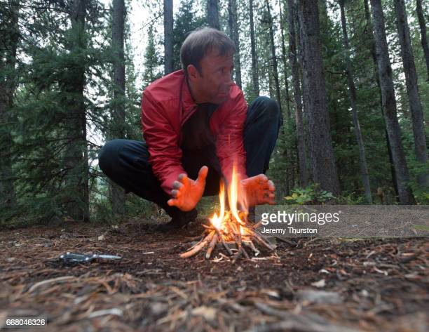 man lost and alone in the woods sits by small fire as night approaches