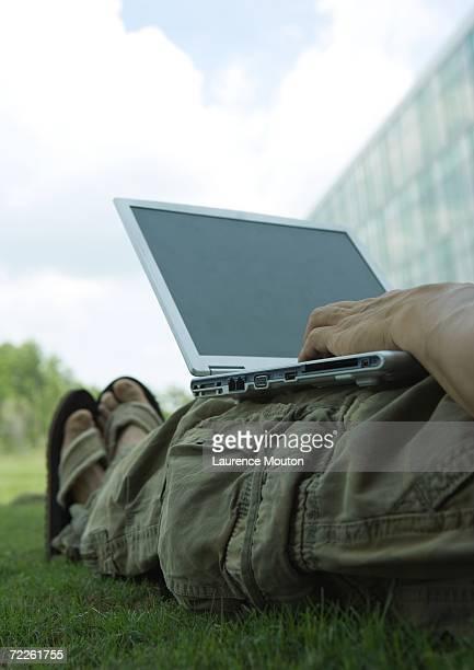 Man lounging in grass, using laptop