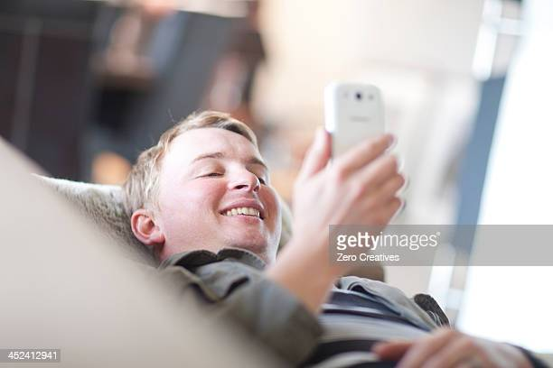 Man lounging on sofa looking at cellphone