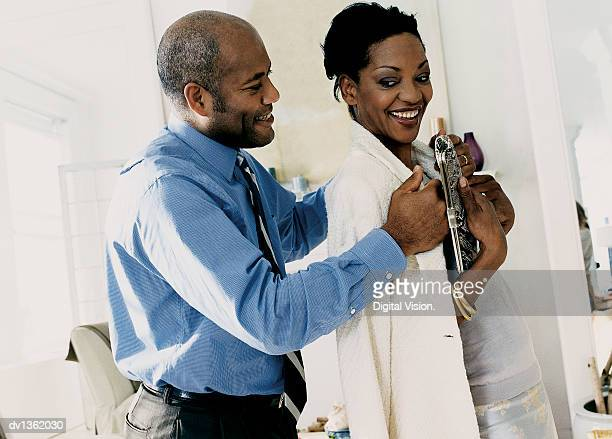 Man Lovingly Helping a Woman Put on Her Jacket in Their Living Room