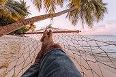 Man lying down on a Hammock in a paradisiac beach at Maldives
