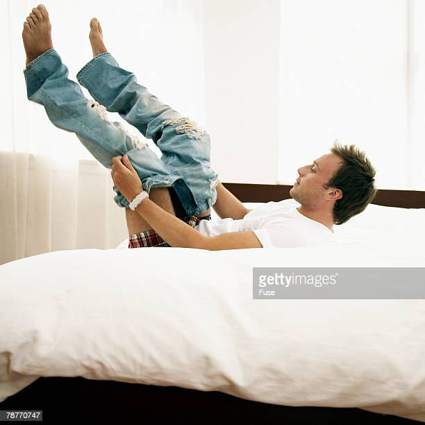 Man Lying Down to Put on Jeans