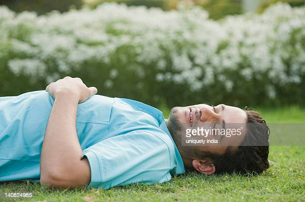 Man lying in a garden and smiling