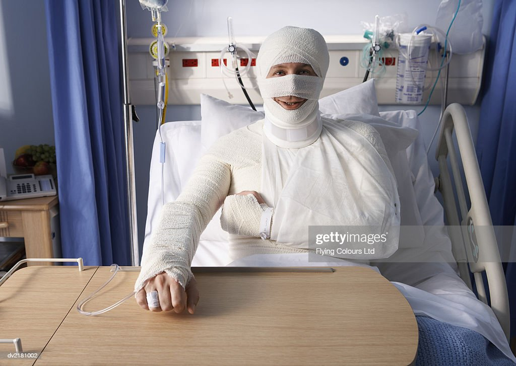 Man Lying In A Hospital Bed Covered In Bandages Stock