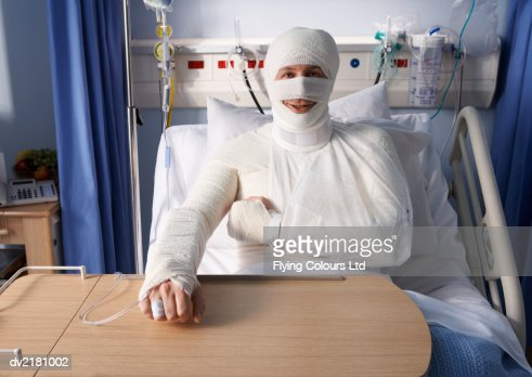 Man Lying in a Hospital Bed, Covered in Bandages