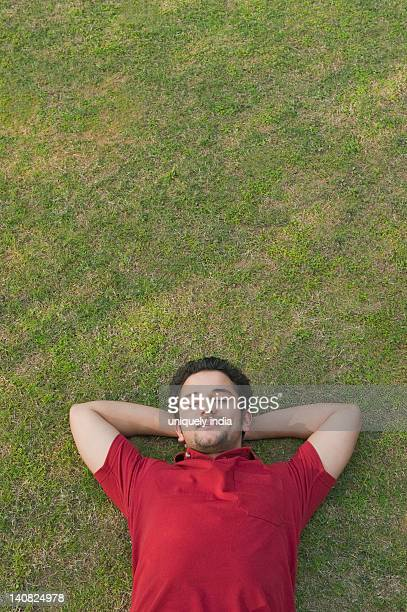 Man lying in a lawn and smiling