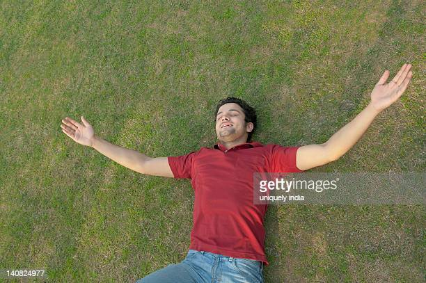 Man lying in a lawn with his arm outstretched