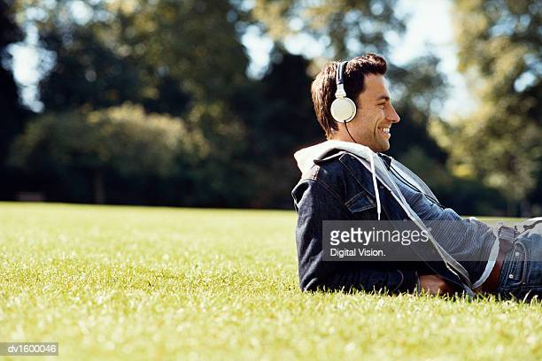 Man Lying in a Park, Leaning on his Elbows, Wearing Headphones