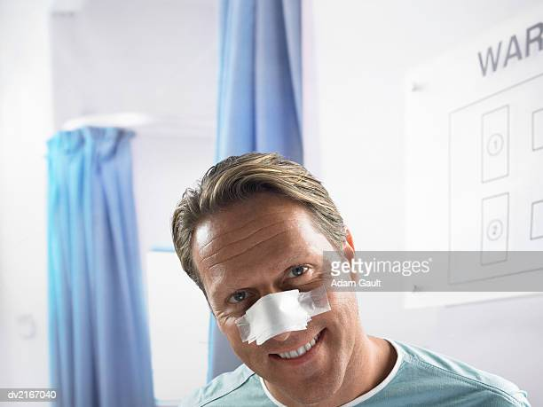 Man Lying in a Ward With a Bandage on His Nose
