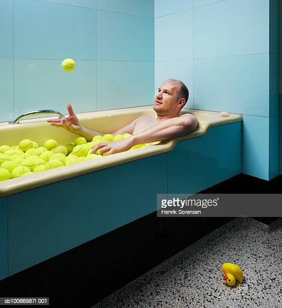 Man lying in bath full of tennis balls